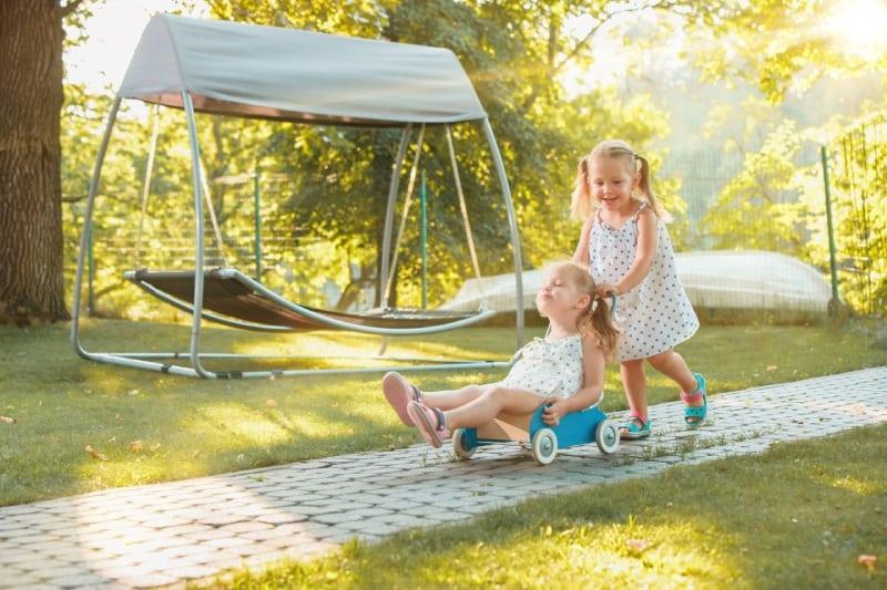 Cute Little Blond Girls Riding Toy Car Summer