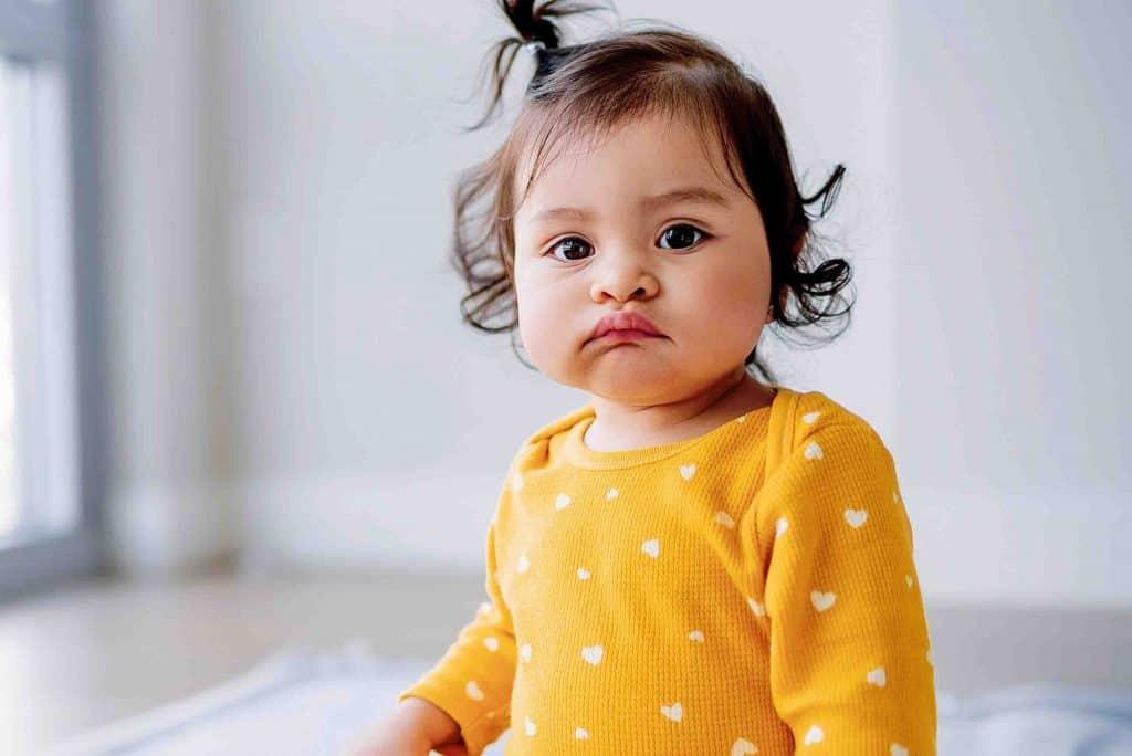 baby in yellow onesie sitting on the floor