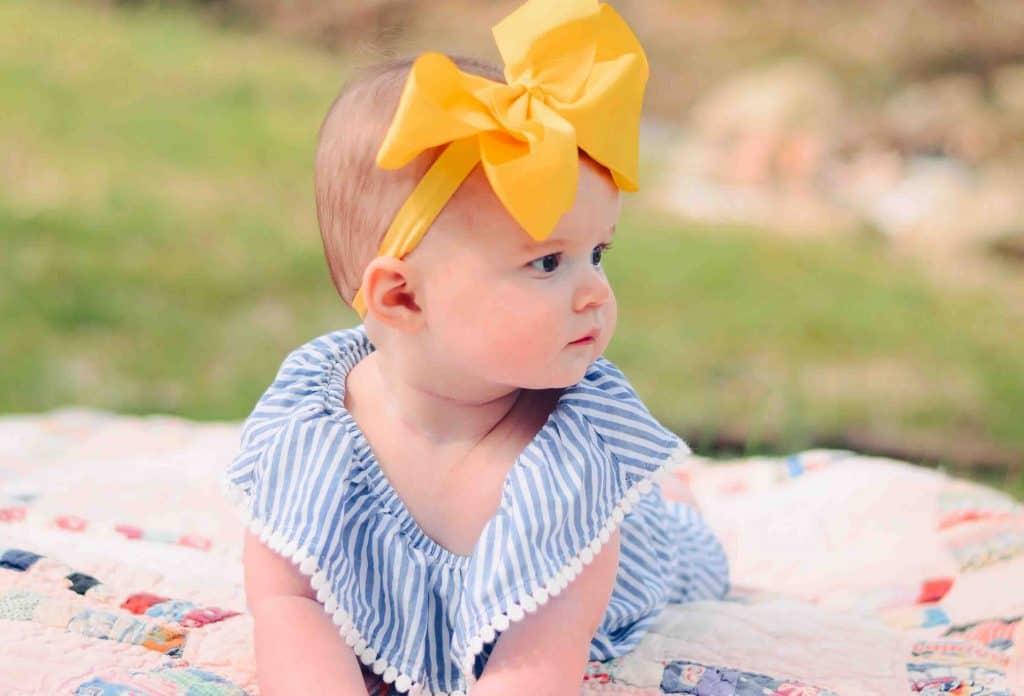 baby wearing a yellow headdress