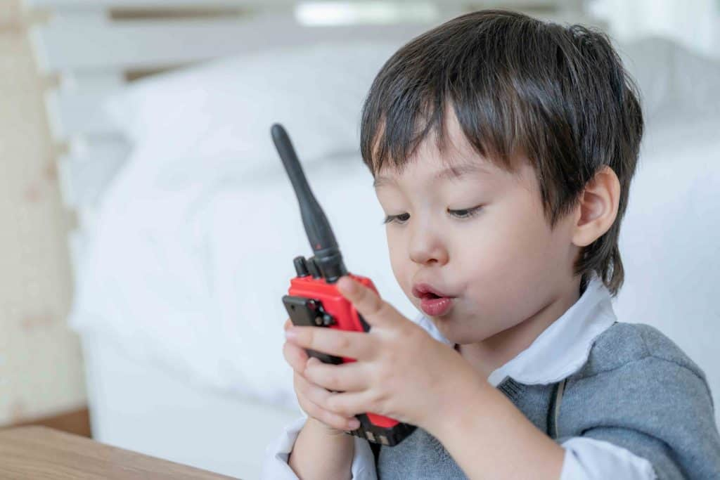 little boy playing with a walkie talkie