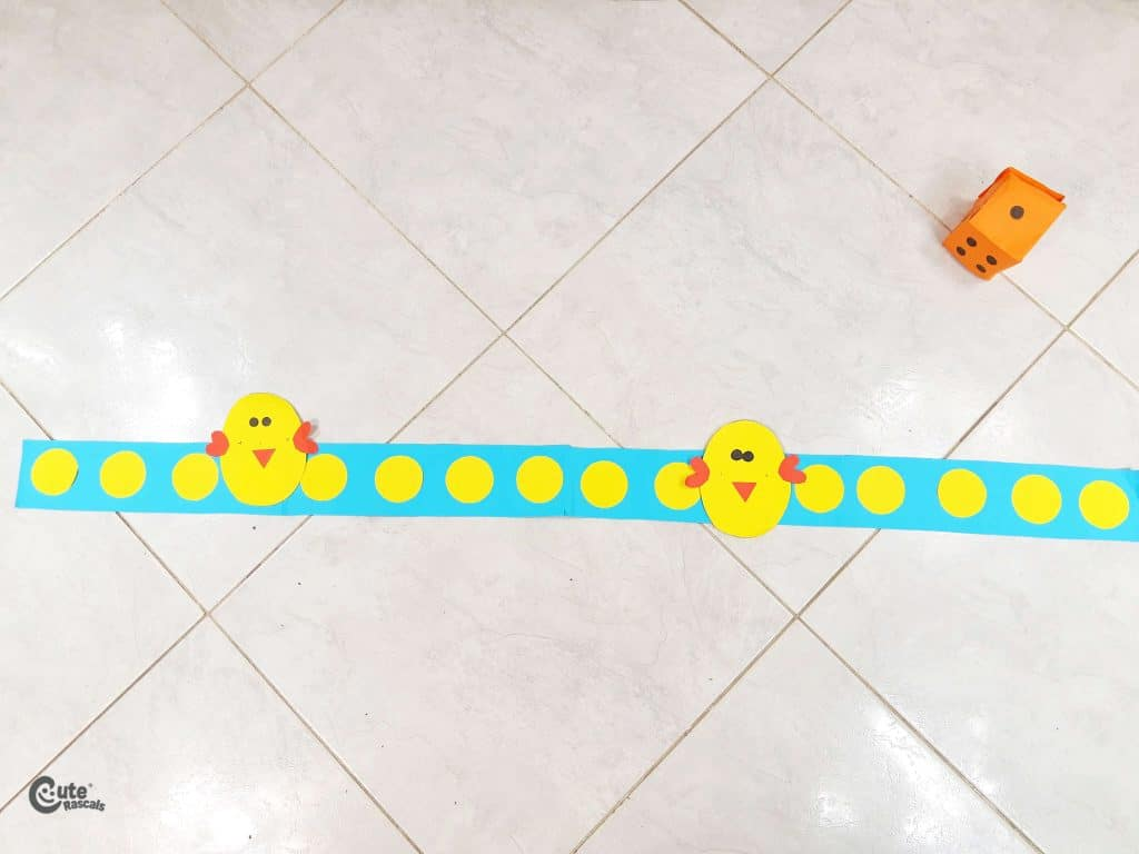 tape the chickens on the construction paper strip