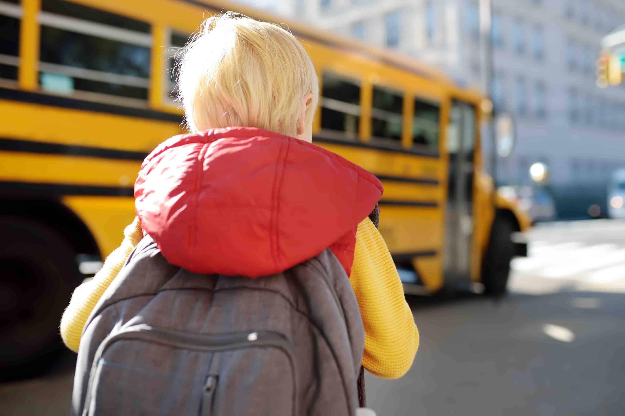 little boy heading towards school bus